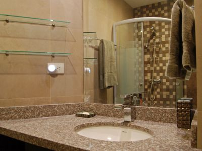 Sink area in 2nd bedroom private bath. Both private bathrooms have glass shelves. Each has a nightli