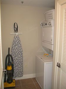 Laundry room with stack washer and dryer, iron & ironing board