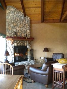 Floor to ceiling rock fireplace adds a warm ambience to the river-front cabin.