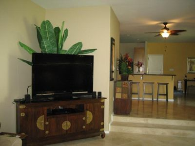 Big screen TV with DVD in living room with view of kitchen counter, bar stools