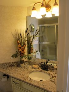 Guest bath has been remodeled with granite and fine fixtures.