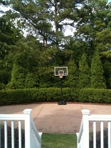 Basketball court/patio, beautiful landscaping, off deck from great room.