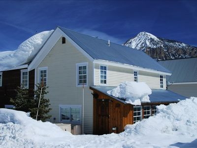 House with Mt Crested Butte to the back. Free bus for ski slopeside delivery.