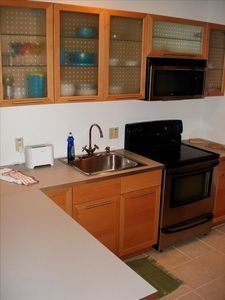 Kitchen has black and stainless steel appliances with beautiful birch cabinets..