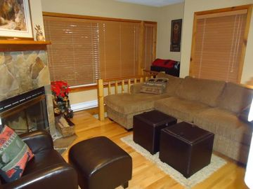 Confortable livingroom with wood blinds and hardwood floors