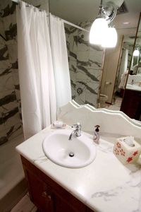 Hall Bath with tub shower marble tiles