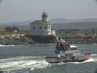 Bandon house photo - Summer Coast Guard 47 crew returning to dock passing Couquille River Lighthouse.