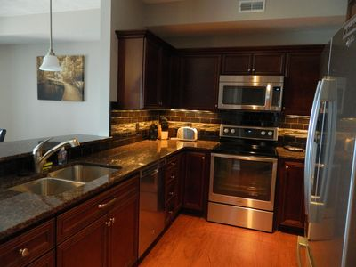 Kitchen with Cherry Cabinets, stainless steel appliances and granite.