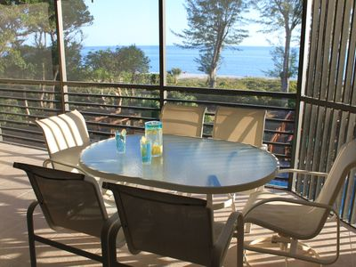 Screened lanai with table, chairs, lounge, and gulf view