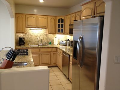 Kitchen with dishwasher, bar sink, granite counter