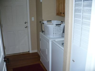 Utility room/ mud room with door to outside, large capacity washer and dryer