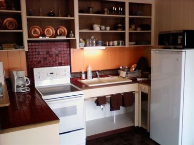 The full service kitchenette opens into the living room and dining area.