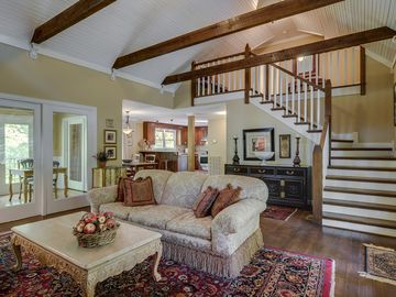Vaulted ceiling with exposed beams. Staircase leads to two bedrooms and bathroom