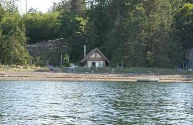 view of the cabin and property from the water