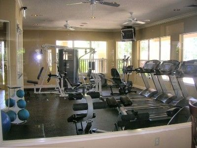Fitness center with TVs and ceiling fans overlooks pool area.