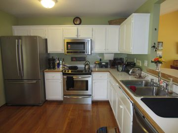 Kitchen appliances -- all stainless steel with toaster, coffee maker, teapot.