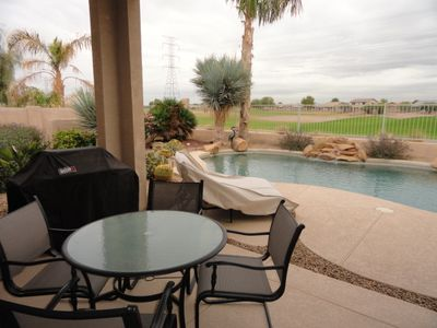 covered patio with weber bbq, comfortable seating including loungers poolside