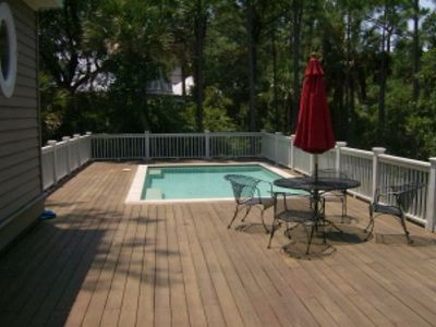 Large pool and deck with outdoor seating for four.