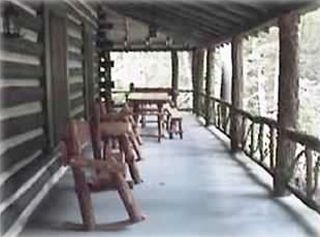 Wrap-around porch with hand-crafted bent-wood rockers and rustic porch furniture