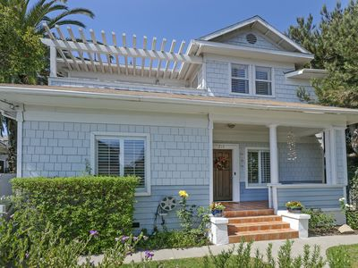 This charming downtown home has a welcoming front porch, gated driveway to the side yard, and the curb appeal of a beach house.