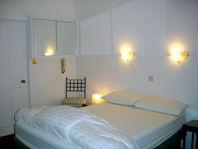 THE BEDROOM with a double bed and a mirrored wall cupboard.