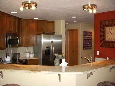 Exquisite open kitchen with granite counter tops and stainless steel appliances.