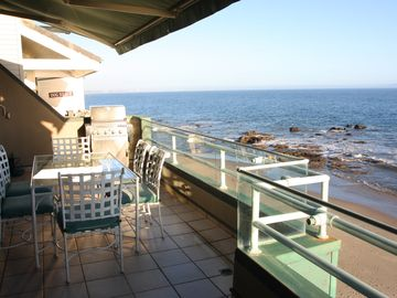 Outdoor dining area with beach below.