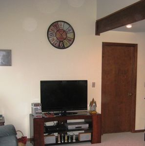 Large flat panel tv located in family room near fireplace and spiral staircase