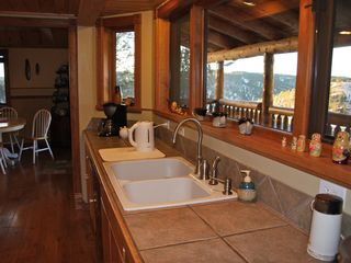 Divide house photo - Sink in kitchen with view of porch and mountains.