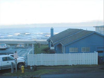 PICTURE OF THE HOUSE, THE WHITE FENCE TO ENCLOSED THE YARD AND THE BEACH.