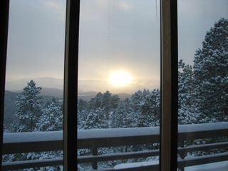 Evergreen house photo - The sun about to set while it's snowing!
