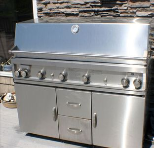 commercial size gas grill on large lakeside deck