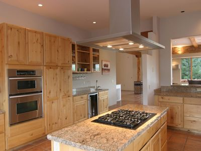 Kitchen with gas range, double ovens, wine cooler, wet bar