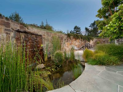 Zen-like patio with organic shape stone wall and waterfall provides great outdoo