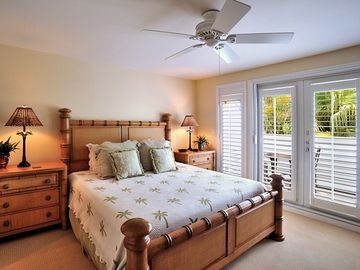 The master bedroom: overhead fan and French doors to private balcony.