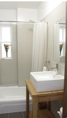 Queens studio photo - Modern Bathroom. Bamboo Vanity. Vessel Sink. High Ceilings. Window with Sunlight