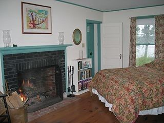 Brunswick house photo - First floor bedroom w/working fireplace, water view & seating area