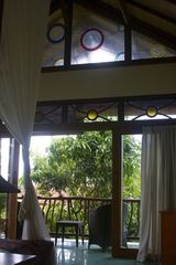 Sanur house photo - Upstairs bedroom. View of stained glass & ventilation windows and balcony.