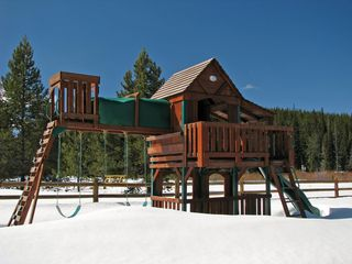 West Yellowstone house photo - Children have a big yard and playground equipment - there's no snow in July:-)