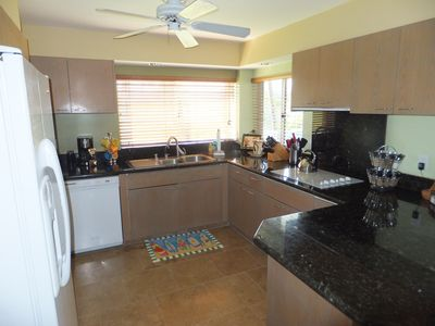 New granite counters and stone flooring in the gourmet kitchen -golf course view