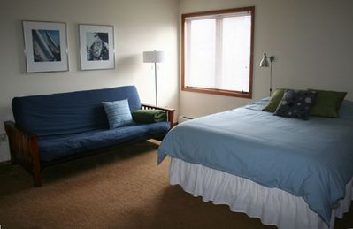 This spacious bedroom has queen bed, private full bathroom, TV and futon seating