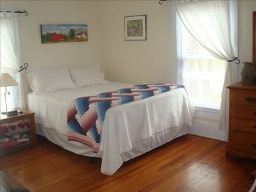 Master Bedroom has queen bed, air conditioner & raised ceiling with ceiling fan.