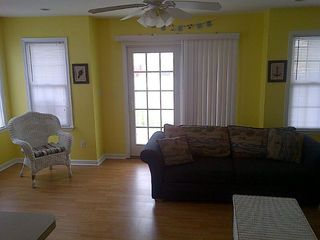 Living room area with new laminate flooring and fresh paint throughout! - Wildwood condo vacation rental photo