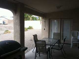 back covered patio with misters tabel for 6 extra chairs and bar and bbq