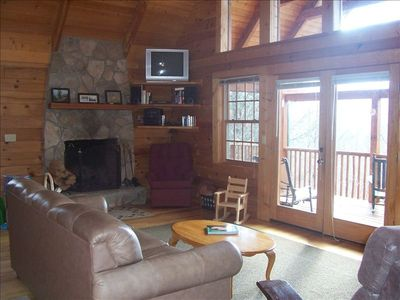 Living area with vaulted ceiling, stone fireplace, fan and full wall of windows!