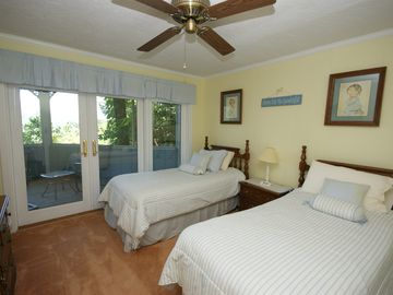 Cute twin beds with ceiling fans and french doors open to screened porch.