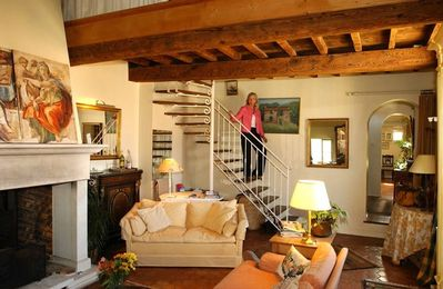 Uzes apartment rental - Part of livingroom with stairs to upper floor, entry and diningroom on far right