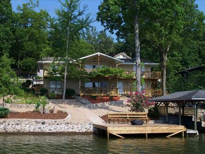 View of the house from the lake, with swimming dock and fire pit
