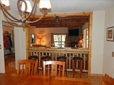 Big dining table and Log bar with views of living room and TV