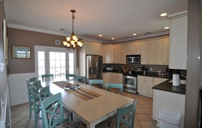 Fully-equipped Kitchen and Dining Area with Ocean View and Deck Access